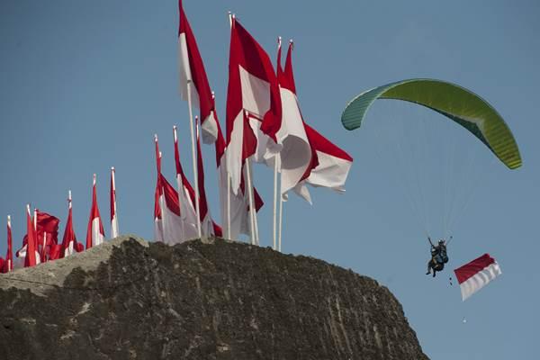 Seorang pecinta paralayang melintas di atas tebing saat pengibaran Bendera Merah Putih terpanjang di Pantai Pandawa, Badung, Bali, Senin (14/8). Pengibaran Bendera Merah Putih sepanjang 800 meter tersebut untuk memperingati HUT ke-72 Proklamasi Kemerdekaan Indonesia, memperkuat nasionalisme dan sekaligus memecahkan rekor MURI. ANTARA FOTO - Nyoman Budhiana