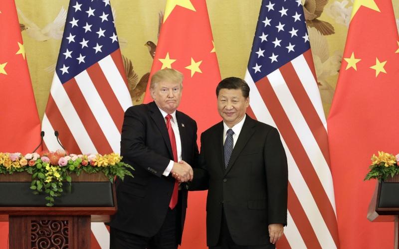 Presiden AS Donald Trump dan Presiden China Xi Jinping bersalaman dalam konferensi pers di Great Hall of the People di Beijing, China, Kamis (9/11/2017). - Bloomberg/Qilai Shen\n