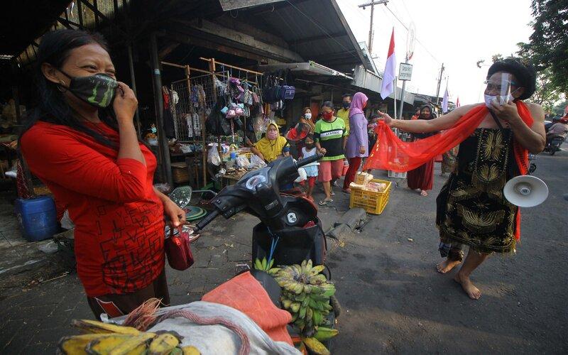 Seniman ludruk Meimura (kanan) mengenakan busana Tari Remo saat aksi blusukan di Pasar Menur, Surabaya, Jawa Timur, Rabu (5/8/2020). Aksi tersebut bertujuan untuk mengajak masyarakat mematuhi protokol kesehatan seperti penggunaan masker, menjaga jarak dan cuci tangan saat beraktivitas di pasar guna mencegah potensi penyebaran Covid-19. - Antara/Moch Asim