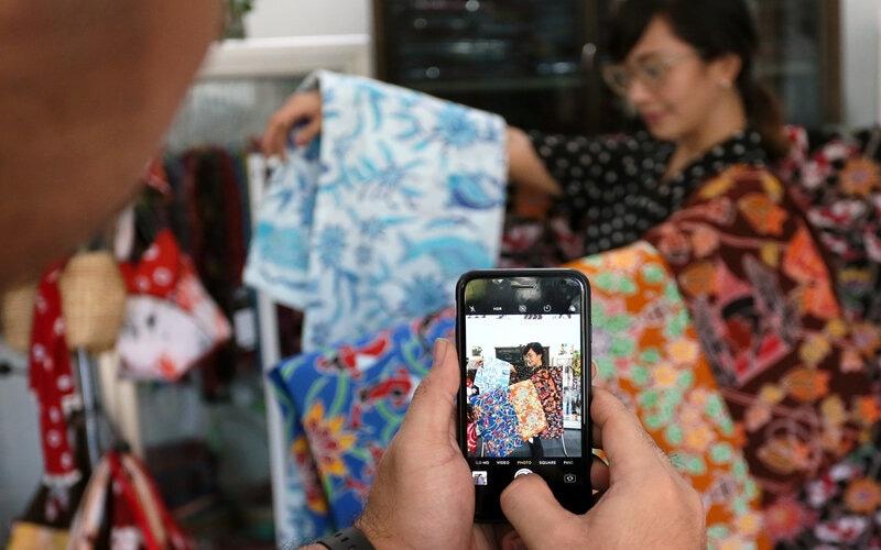 Perajin batik khas Blitar Yogi Rosdianta memotret istrinya Santika sambil memegang batik hasil produksinya menggunakan gawai untuk diunggah ke pasar digital di sentra kerajinan batik khas Blitar Mawar Putih, di Blitar, Jawa Timur, Rabu (5/8/2020). - Antara/Irfan Anshori