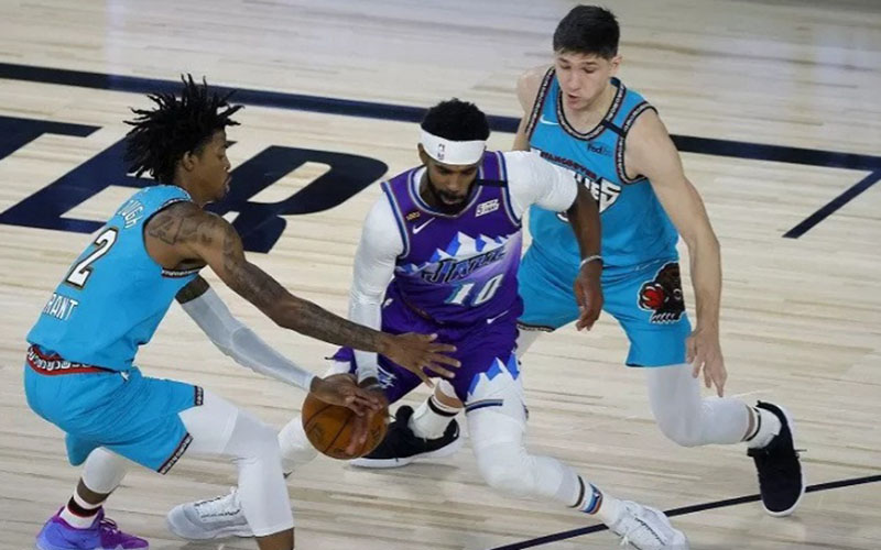 Pebasket Utah Jazz Mike Conley (tengah) berusaha menjaga penguasaan bola di tengah kawalan dua pemain Memphis Grizzlies, Ja Morant (kiri) dan Grayson Allen./Antara - Reuters