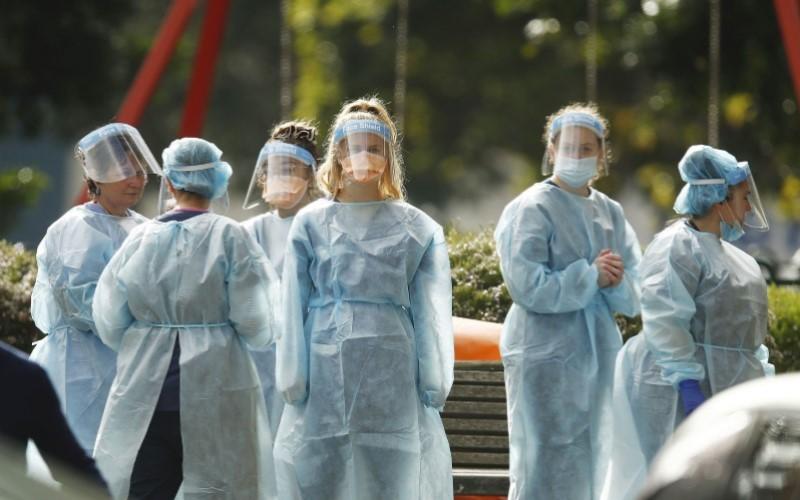 Petugas medis di Victoria, Australia, sedang mengenakan APD - Bloomberg