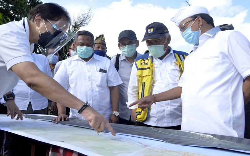 Menteri Pekerjaan Umum dan Perumahan Rakyat (PUPR) Basuki Hadimuljono (kedua kanan) didampingi Gubernur Bali Wayan Koster (kanan) mengamati rencana pembangunan Tol Denpasar-Gilimanuk di kawasan Mengwi, Badung, Bali, Kamis (6/8/2020). Tol sepanjang 95 kilometer yang menghubungkan kawasan Mengwi dengan Pelabuhan Gilimanuk, Jembrana tersebut rencananya akan mulai dikerjakan dalam tiga tahapan mulai bulan Maret tahun 2021 dan ditargetkan selesai pada awal tahun 2024. - Antara/Fikri Yusuf
