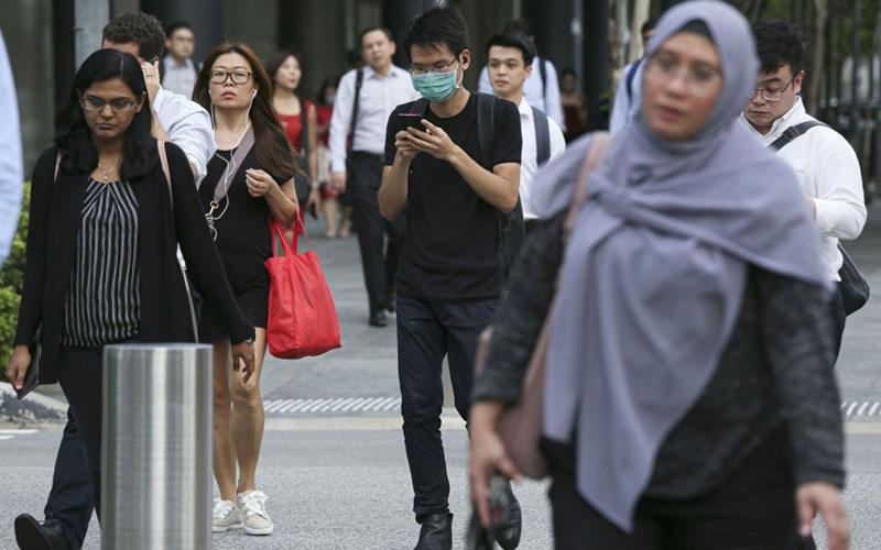 Sejumlah orang berjalan di Marina Bay Singapura pada 12 Februari 2020, ketika wabah corona mulai menyergap negara pulau itu. - Bloomberg