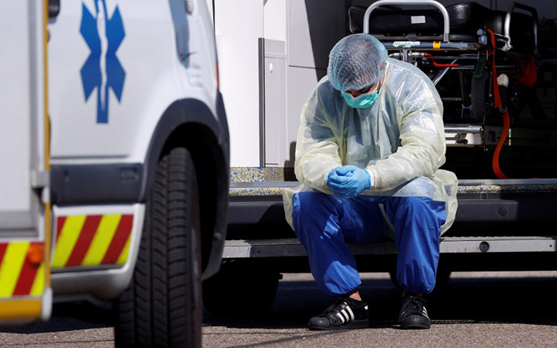 Petugas medis dengan alat pelindung diri beristirahat selama pemindahan pasien yang terinfeksi virus Corona dari Strasbourg di Prancis, Senin (30/3/2020), menuju Jerman dan Swiss./Antara - Reuters