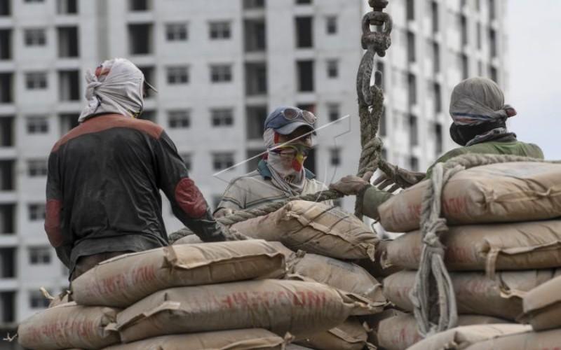 Pekerja melakukan bongkar muat semen kedalam kapal di Pelabuhan Sunda Kelapa, Jakarta, Jumat (14/2/2020). Pemerintah akan melakukan sosialisasi secara rinci kepada masyarakat Indonesia terkait Omnimbus Law Rancangan Undang-Undang (RUU) Cipta Kerja. ANTARA FOTO/Hafidz Mubarak A - ama