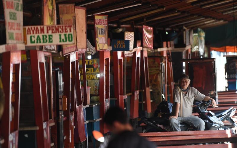 Seorang pria duduk di deretan warung kaki lima yang tutup menyusul sepinya pengunjung akibat pandemi COVID-19 di Jakarta, Kamis (2/4/2020). Minimnya aktivitas perkantoran di Jakarta akibat pandemi COVID-19 membuat sejumlah pedagang warung kaki lima memilih untuk menutup dagangannya dan mudik ke kampung halaman. - ANTARA FOTO/Akbar Nugroho Gumay
