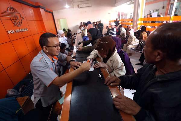 Ilustrasi - Warga mengantri melakukan pencairan tunjangan bagi pegawai negeri sipil (PNS) maupun TNI dan Polri yang berupa gaji ke 13 di Kantor Pos.  - Bisnis.com