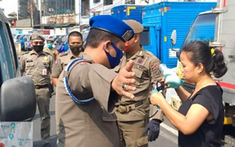 Satuan Polisi Pamong Praja Jakarta Barat saat menggelar razia masker di Pasar Pagi Asemka, Tamansari, Jakarta Barat, Selasa (21/7/2020). - Antara/Satpol PP Jakarta Barat