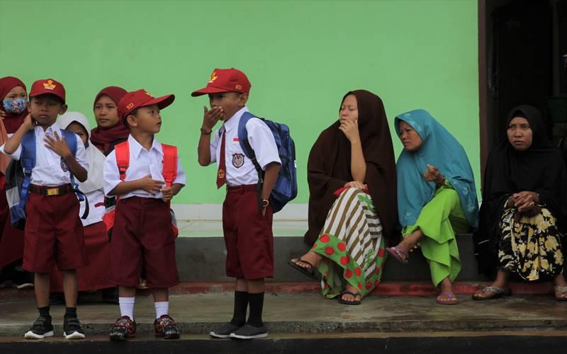 Sejumlah orang tua murid menunggu anaknya saat bersekolah pada hari pertama tahun ajaran baru di SD Negeri 1 Praja Taman Sari di Desa Wonuamonapa, Konawe, Sulawesi Tenggara, Senin (13/7/2020). Pihak sekolah terpaksa menerapkan pembelajaran dengan tiga kali pertemuan tatap muka di sekolah dalam sepekan karena terbatasnya jaringan telekomunikasi untuk penerapan pembelajaran jarak jauh secara daring guna mencegah penyebaran COVID-19. ANTARA FOTO - Jojon