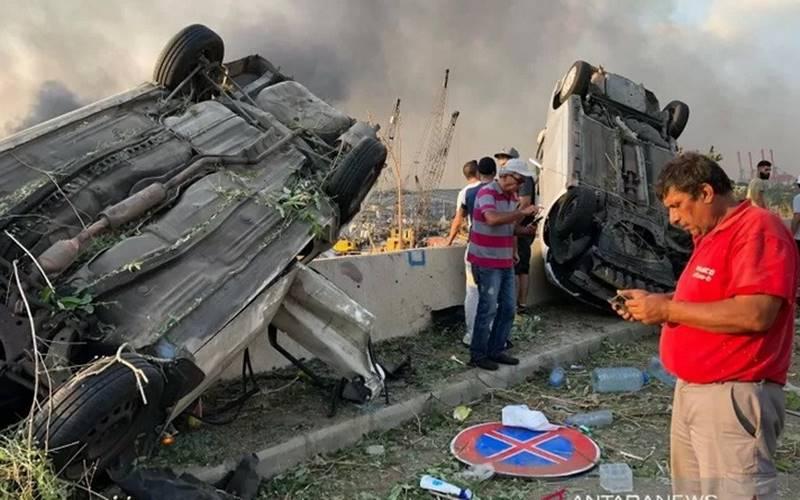 Warga berdiri di dekat mobil yang hancur akibat ledakan gudang bahan peledak di Beirut, Lebanon, Selasa (4/8/2020). - Antara/Reuters