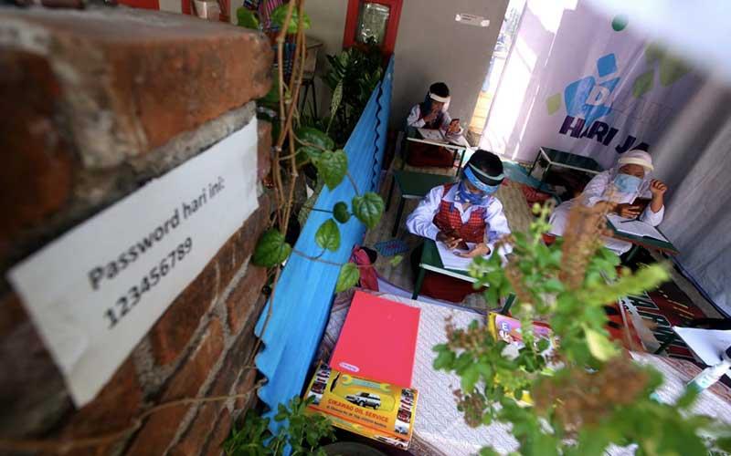 Siswa Sekolah Dasar (SD) melakukan pembelajaran jarak jauh menggunakan kuota internet secara gratis di Warung Internet Covid-19 RW 09 Kelurahan Lingkar Selatan, Bandung, Jawa Barat, Senin (10/8/2020). Bisnis - Rachman