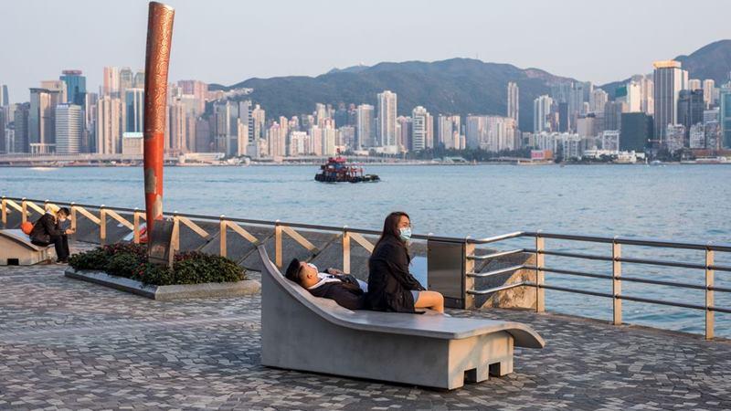 Pengunjung duduk di tepi pantai di Victoria Harbour di distrik Tsim Sha Tsui di Hong Kong pada 29 Januari 2020. -  Paul Yeung / Bloomberg