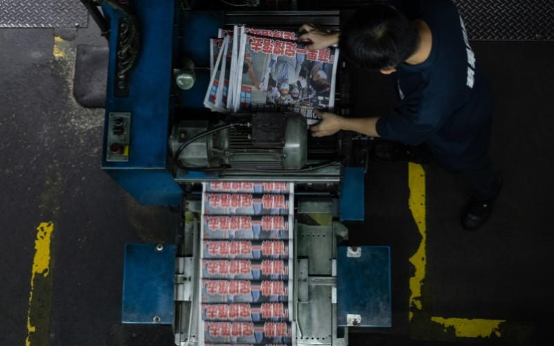 Pekerja sedang mengoperasikan mesin cetak koran di Hong Kong - Bloomberg
