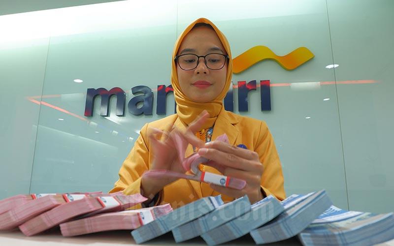 Karyawan menghitung uang pecahan Rp100.000 disalah satu kantor cabang milik PT Bank Mandiri (Persero) Tbk yang ada di Jakarta, Senin (7/10). Bisnis - Nurul Hidayat