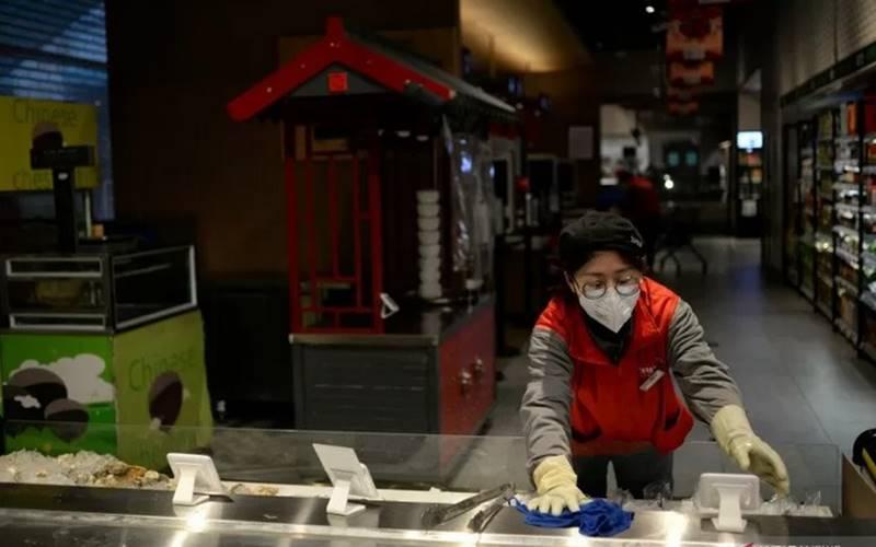 Seorang anggota staf membersihkan konter bagian makanan laut di jaringan 7Fresh JD.com sebelum toko dibuka, saat negeri tersebut sedang dilanda penularan virus corona baru, di Kota Yizhuang, Beijing, China, Sabtu (8/2/2020). Foto diambil tanggal 8 Februari 2020.  - Antara/Reuters