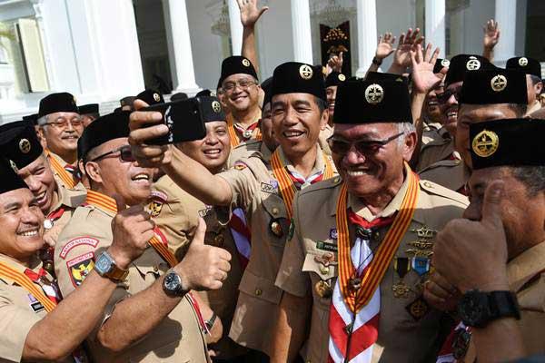 Ilustrasi - Presiden Joko Widodo (tengah) berswafoto dengan pengurus Kwartir Nasional Gerakan Pramuka seusai pelantikan di Halaman Istana Merdeka, Jakarta, Kamis (27/12/2018). - ANTARA/Wahyu Putro A
