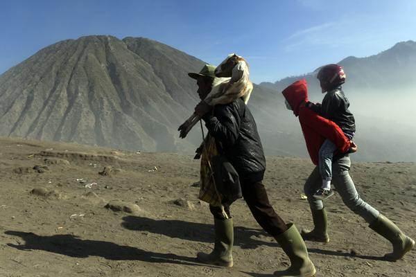 Warga Suku Tengger memanggul kambing sesaji yang akan dilarung di kawah Gunung Bromo saat Upacara Yadnya Kasada di Gunung Bromo, Probolinggo. - Antara/Zabur Karuru