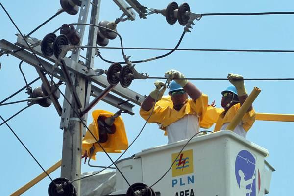 Teknisi Pengerjaan Dalam Keadaan Bertegangan (PDKB) mengerjakan perawatan jaringan listrik.  - BISNIS