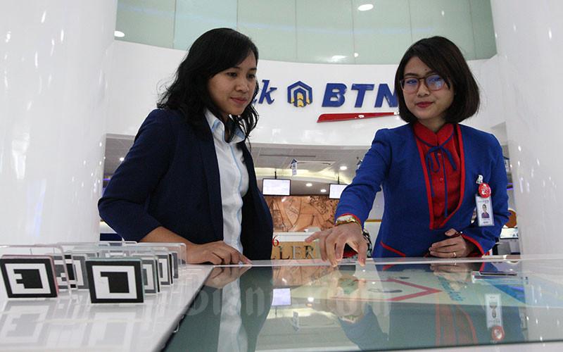 Karyawati PT Bank Tabungan Negara memberikan penjelasan mengenai produk perbankan kepada nasabah di Jakarta, Senin (8/1). Bisnis - Dedi Gunawan