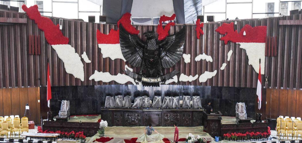 Pekerja memasang penutup karpet merah di ruang rapat paripurna Gedung Nusantara, Kompleks Parlemen, Senayan, Jakarta, Selasa (14/8/2018). - Antara / Hafidz Mubarak A.