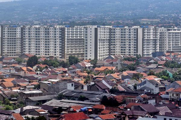 Bangunan hunian vertikal berdiri di antara kawasan padat penduduk di Bandung, Jawa Barat, Sabtu (11/3). - Antara/Aditya Pradana Putra