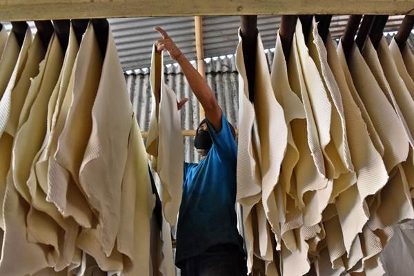 Buruh mengecek lembaran karet yang baru saja dicetak di pabrik pengolahan karet di Kabupaten Semarang, Jawa Tengah./Antra - Aditya Pradana Putra