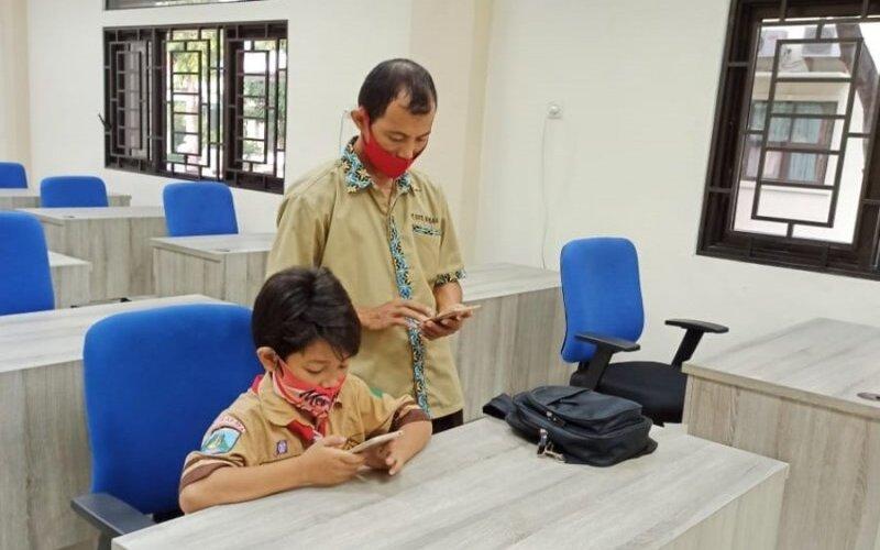 Seorang siswa menggunakan fasilitas akses internet gratis yang disediakan di Kantor BPSDM Jawa Timur di Jalan Balongsari Tama Surabaya, Jumat (14/08/2020). - Antara/BPSDM Jatim