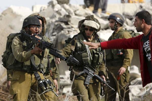Seorang pria Palestina berdebat dengan tentara Israel ketika penghancuran rumah seorang Palestina atas perintah pasukan Israel saat ia mencoba menghentikan penghancuran tersebut di desa Biet Ula Tepi Barat, barat Hebron, Kamis (21/1). - Reuters