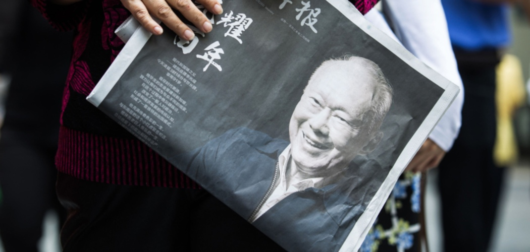 Warga membawa koran bersampulkan foto Lee Kuan Yew setelah Bapak Singapura itu meninggal dunia, di Singapura, Senin (23/3/2015). - Bloomberg/Nicky Loh