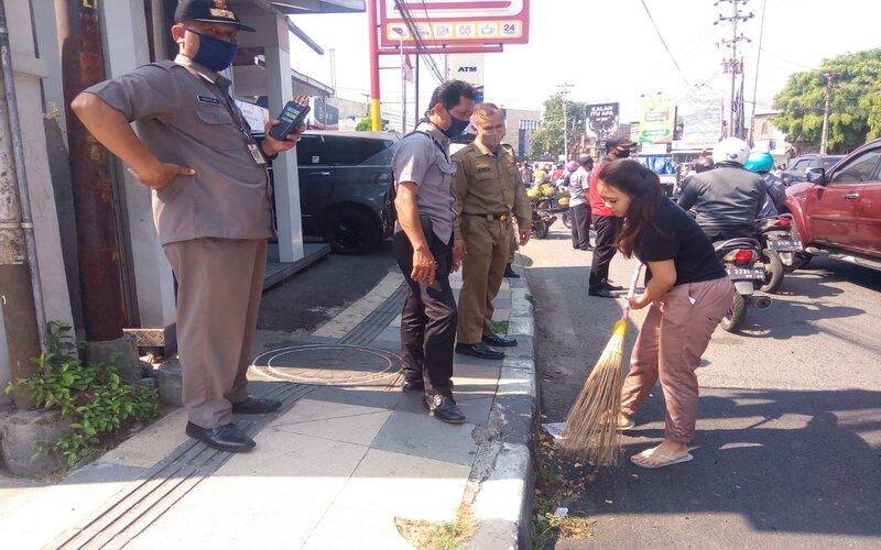Warga tak mengenakan masker dihukum menyapu jalan di Semarang, Selasa (18/8/2020). - Bisnis/Alif N.