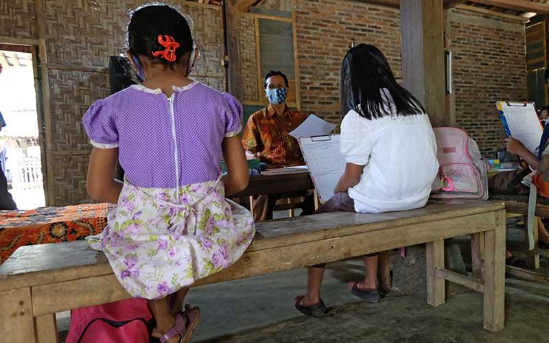 Guru SD Kanisius Kenalan Henricus Suroto (tengah) mengajar secara tatap muka dengan mendatangi murid-muridnya dari rumah ke rumah. ANTARA FOTO - Anis Efizudin