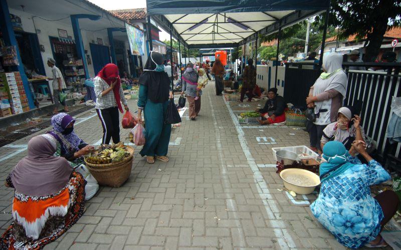 Sejumlah pedagang menunggu pembeli di Pasar Bandung Kimpling, Tegal, Jawa Tengah, Sabtu (2/5/2020). Pemerintah Kota Tegal menata para pedagang di lima pasar dengan menerapkan jaga jarak 1 meter antarpedagang sebagai upaya pencegahan penyebaran Covid-19. - ANTARA