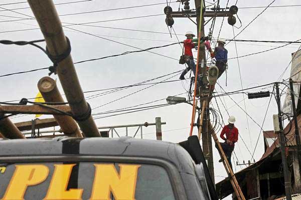 Pekerja melakukan perawatan dan pemasangan jaringan kabel listrik.  - ANTARA/Syifa Yulinnas