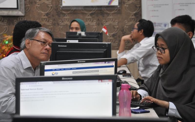 Petugas Pajak melayani wajib pajak untuk mengisi form pelaporan SPT Pajak Tahunan melalui daring di Kantor Wilayah Direktorat Jenderal Pajak (DJP) Sumut I di Medan, Sumatera Utara, Senin (2/3/2020). - ANTARA FOTO/Septianda Perdana