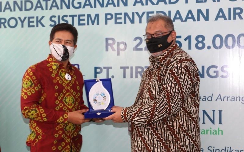 Pemimpin Divisi Komersial BNI Syariah, Daryanto Tri Sumardono (kanan) ketika menerima plakat dari PT PP Infrastruktur yang diserahkan oleh Direktur Keuangan PT PP Infrastruktur, I Komang Sudarma (kiri) dalam acara penandatangan perjanjian pembiayaan investasi di Kantor PT Tirta Tangsel Mandiri, Rabu (19/8) - dokumen BNI Syariah
