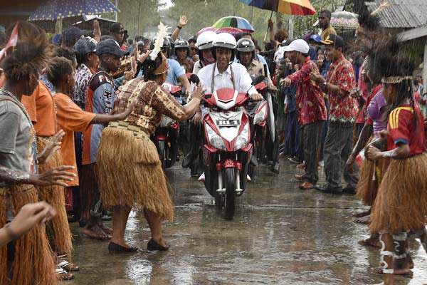 Presiden Joko Widodo berboncengan sepeda motor dengan Ibu Negara Iriana Joko Widodo saat kunjungan kerja di Distrik Agats, Kabupaten Asmat, Papua, Kamis (12/4/2018). - Antara/Puspa Perwitasari