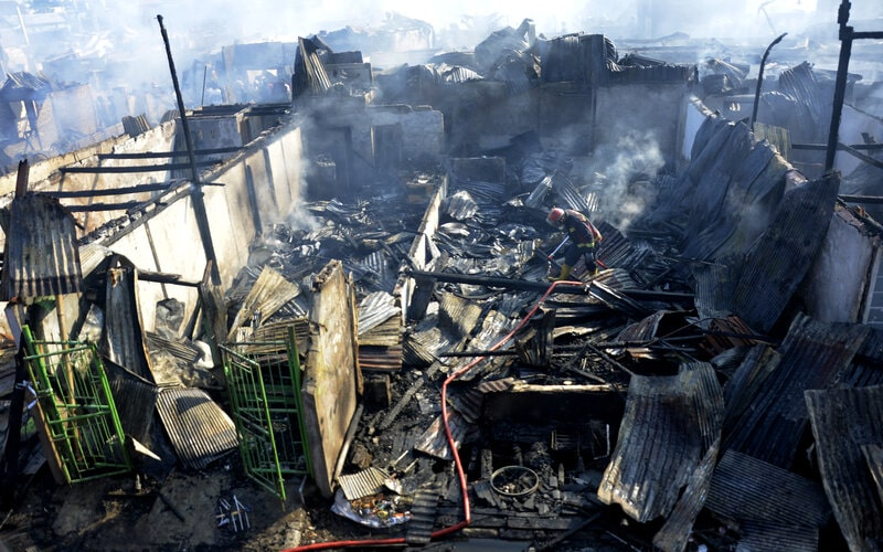 Petugas Pemadam Kebakaran melakukan pendinginan di lokasi rumah yang terbakar di kawasan Pasar Pannampu, Makassar, Sulawesi Selatan, Minggu (23/8/2020). Kebakaran yang terjadi di pemukiman padat penduduk tersebut menghanguskan puluhan unit rumah warga sementara penyebab kebakaran masih dalam penyelidikan kepolisian. - Antara/Abriawan Abhe