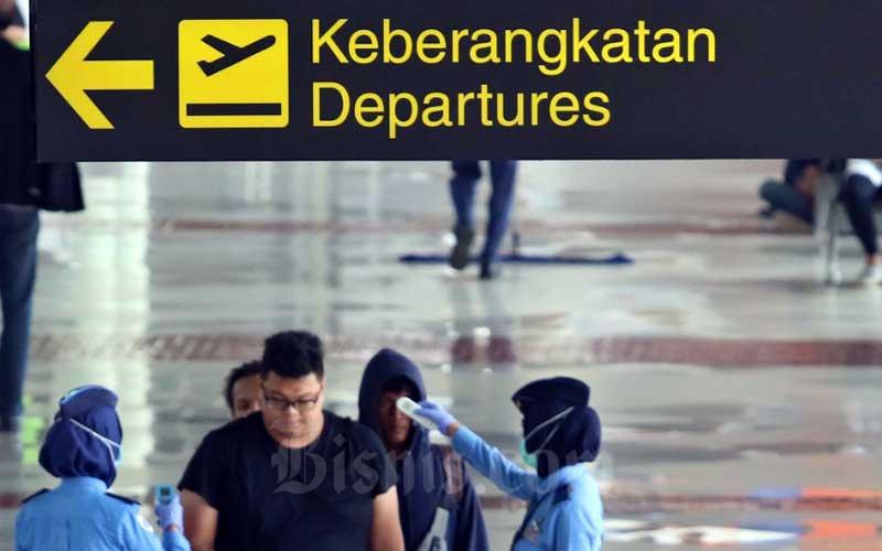 Petugas memeriksa suhu tubuh penumpang yang akan masuk di Terminal IA Bandara Soekarno Hatta, Tangerang, Banten, Selasa (17/3/2020). Bisnis - Eusebio Chrysnamurti
