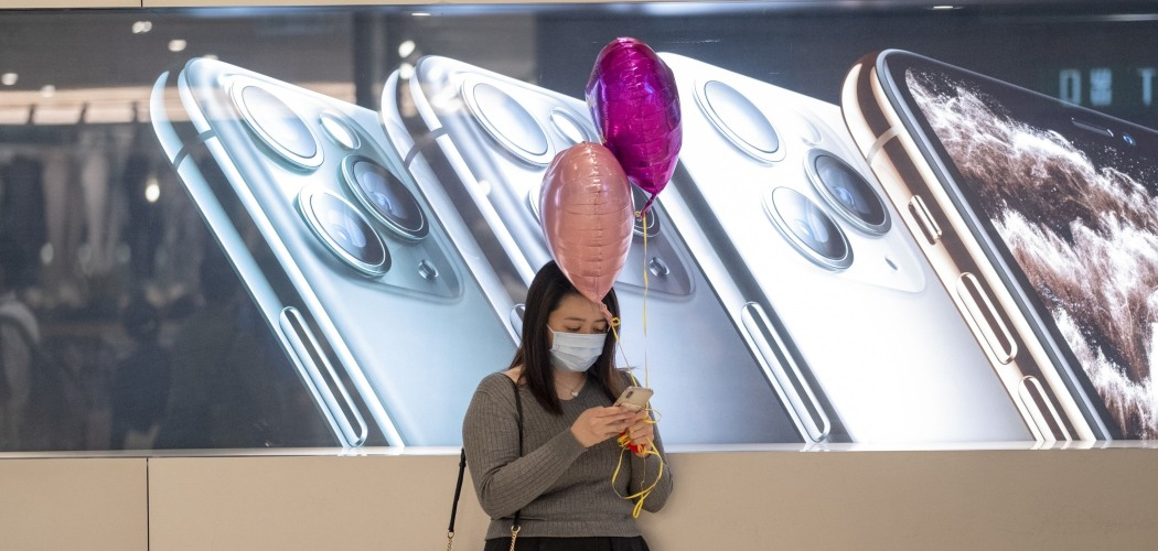 Warga Hong Kong menggunakan ponselnya di depan papan iklan iPhone buatan Apple Inc. di Hong Kong, China, Jumat (14/2/2020). - Bloomberg/Justin Chin