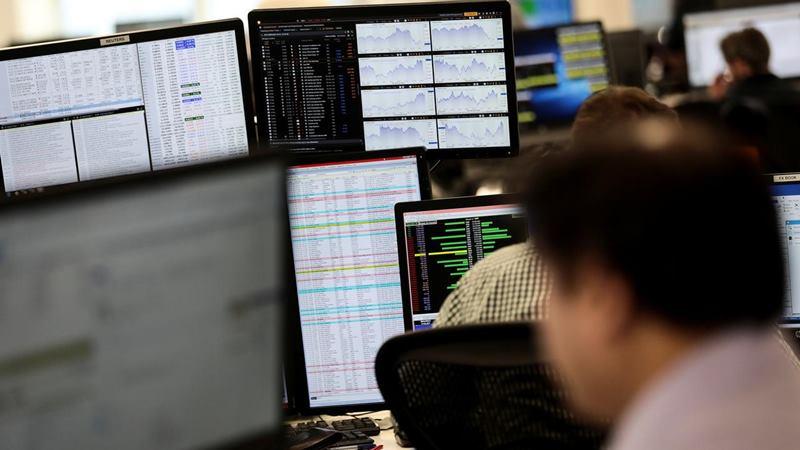 Trader melihat monitor di London. - Reuters