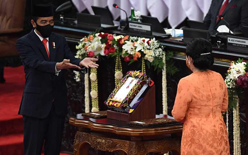Presiden Joko Widodo (kiri) menyerahkan RUU tentang APBN tahun anggaran 2021 beserta nota keuangan dan dokumen pendukungnya kepada Ketua DPR Puan Maharani (kanan) padapembukaan masa persidangan I DPR tahun 2020-2021 di Kompleks Parlemen, Senayan, Jakarta, Jumat (14/8/2020). ANTARA FOTO - Akbar Nugroho Gumay