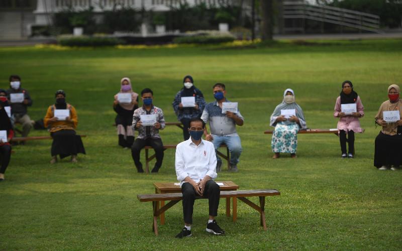 Presiden Joko Widodo (tengah) berfoto bersama usai memberikan bantuan modal kerja kepada pedagang kecil yang terdampak COVID-19 di halaman tengah Istana Merdeka, Jakarta, Selasa (21/7/2020). Presiden memberikan bantuan sebesar Rp2,4 juta kepada masing-masing pedagang.  - ANTARA