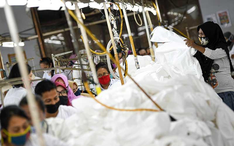 Pekerja perempuan memproduksi alat pelindung diri sebuah perusahaan garmen saat kunjungan Menteri Ketenagakerjaan Ida Fauziyah di Jakarta, Rabu (1/7 - 2020). Pemerintah telah menganggarkan Rp37,7 triliun untuk program subsidi pekerja terdampak Covid/19.  ANTARA