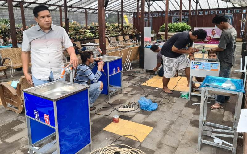 Choliq (kiri) sedang memantau pembuatan wastafel portabel minim sentuhan yang dikerjakan para pegawai BUM/Des Tridadi Makmur.Foto: Istimewa