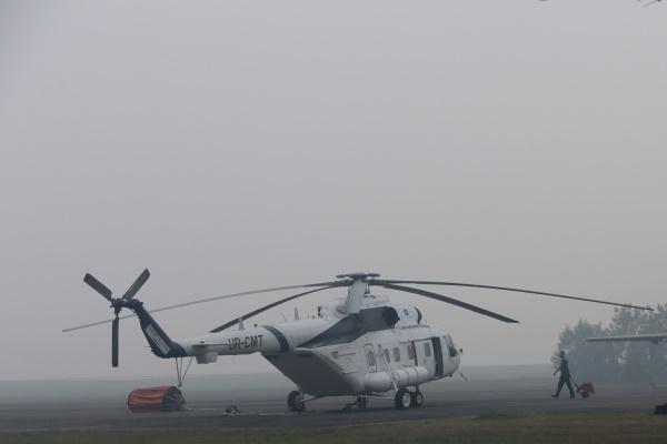 Teknisi Helikopter MI 171 milik BNPB (Badan Nasional Penanggulangan Bencana) memeriksa mesin Helikopter MI 171 di Base Off Landasan Udara TNI AU Palembang yang diselimuti kabut asap, Sumatera Selatan, Kamis (27/8). Helikopter tersebut menunggu jarak pandang membaik untuk melakukan pemadaman kebakaran lahan melalui udara (water boombing) dikarenakan jarak pandang yang menurun hingga 400 meter pada pagi hari karena kabut asap. - Antara/Nova Wahyudi