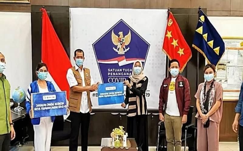 Vice President General Secretary Danone Indonesia, Vera Galuh Sugijanto (ke-4 dari kanan) menyerahkan donasi kepada Kepala Satgas Penanganan Covid-19 RI Doni Monardo (ke-3 dari kiri) di kantor BNPB pada Senin (24/8/2020). - Antara
