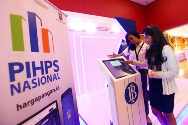 Karyawati melihat harga-harga produk pangan pada layar Pusat Informasi Harga Pangan Strategis (PIHPS) Nasional seusai diluncurkan di Jakarta, Senin (12/6). - JIBI/Dwi Prasetya