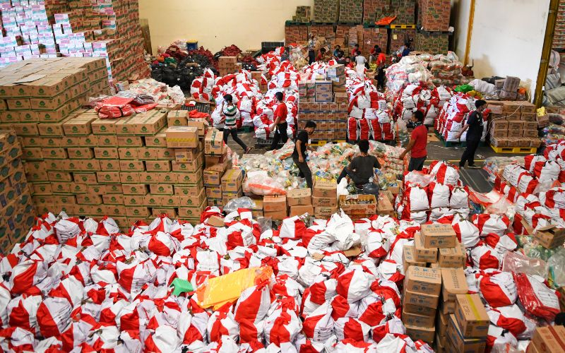Pekerja mengemas paket bantuan sosial (bansos) di Gudang Food Station Cipinang, Jakarta, Rabu (22/4/2020). - Antara/M Risyal Hidayat