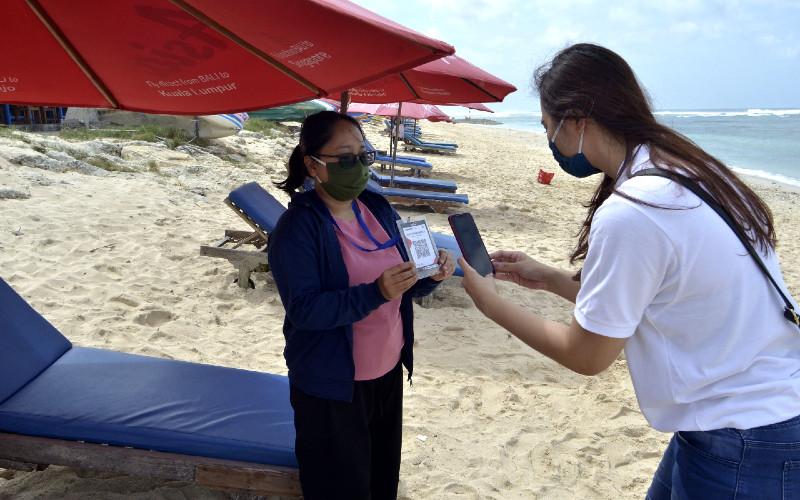Pengunjung melakukan transaksi pembayaran berbasis digital dengan pedagang pantai menggunakan Quick Response Code Indonesian Standard (QRIS) di Pantai Pandawa, Badung, Bali, Sabtu (11/7/2020). - ANTARA